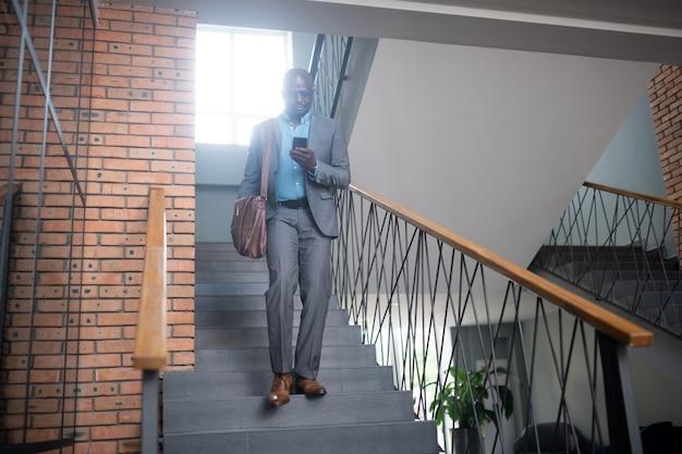 Empresário ocupado. empresário afro-americano ocupado, vestindo terno cinza, lendo mensagem no telefone