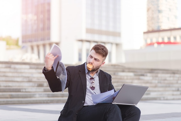 Empresário ocupado senta-se no fundo com um notebook no colo