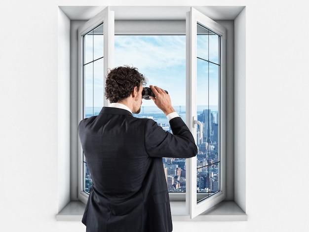 Empresário olha para a cidade da janela do build com binóculos