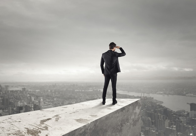 Empresário olha para a cidade do telhado acima da cidade