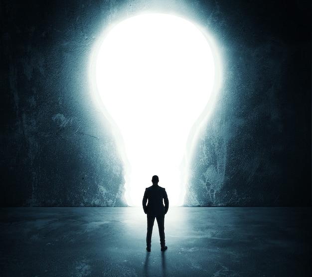 Empresário olha para um grande buraco em forma de lâmpada na parede