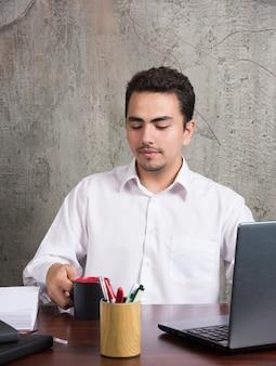 Empresário, olhando a xícara de chá na mesa do escritório.