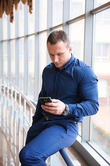 Empresário, olhando através do telefone pela janela