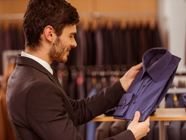 Empresário, olhando e escolhendo a camisa clássica.