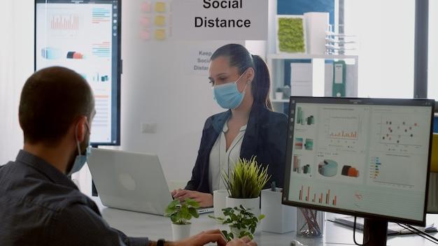 Empresário, olhando gráficos financeiros no monitor do computador enquanto fala com um colega de trabalho sentado no escritório da empresa. colegas com máscaras mantendo o distanciamento social para prevenir a doença covid19
