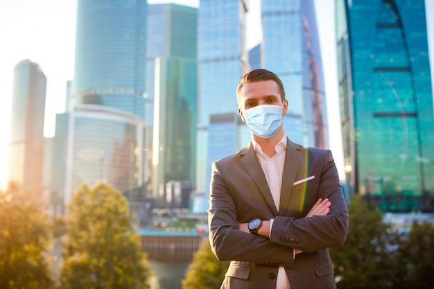 Empresário, olhando no espaço da cópia em pé contra um arranha-céu de vidro