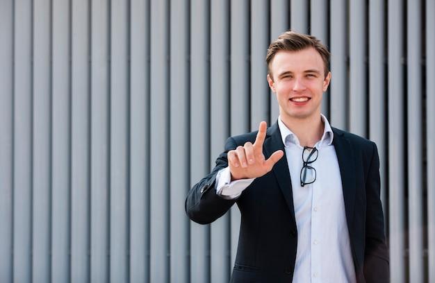Empresário, olhando para a câmera com dois dedos