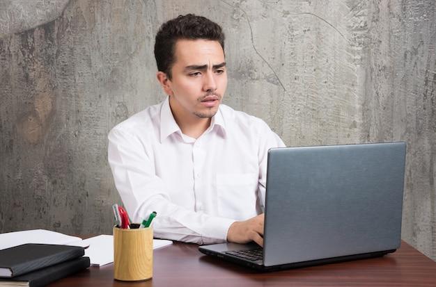 Empresário, olhando para o laptop e sentado à mesa. foto de alta qualidade Foto gratuita