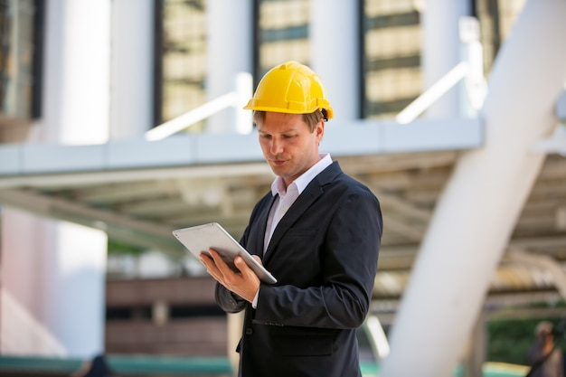 Empresário ou capataz com capacete olhando no plano contra construção