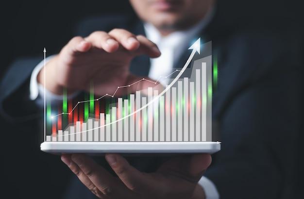 Empresário ou comerciante está mostrando um estoque crescente de holograma virtual. , planejamento e estratégia, mercado de ações, crescimento do negócio, conceito de progresso ou sucesso. , investir em negociação.