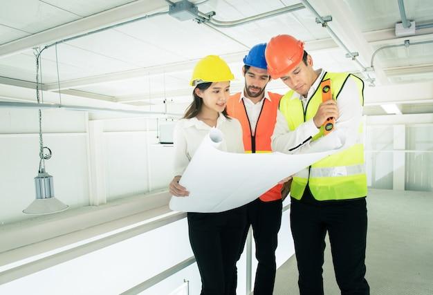 Empresário ou engenheiro arquiteto de raça mista jovem homem caucasiano e mulher asiática usam capacete falando com arquitetos no canteiro de obras