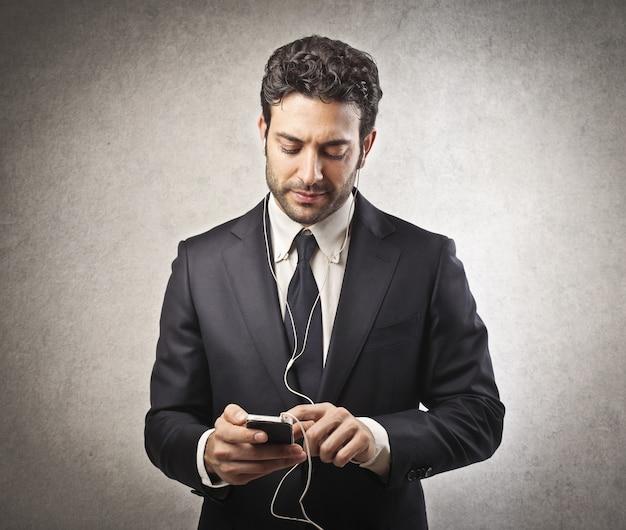Empresário, ouvindo música no smartphone