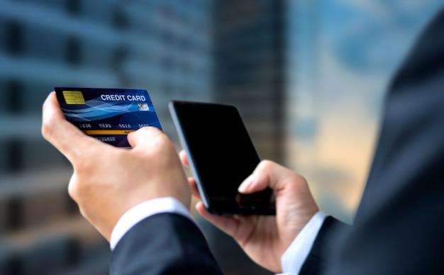 Empresário pagar ou fazer compras por cartão de crédito com smartphone