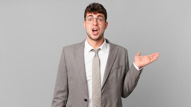 Empresário parecendo surpreso e chocado, com o queixo caído segurando um objeto com a mão aberta na lateral