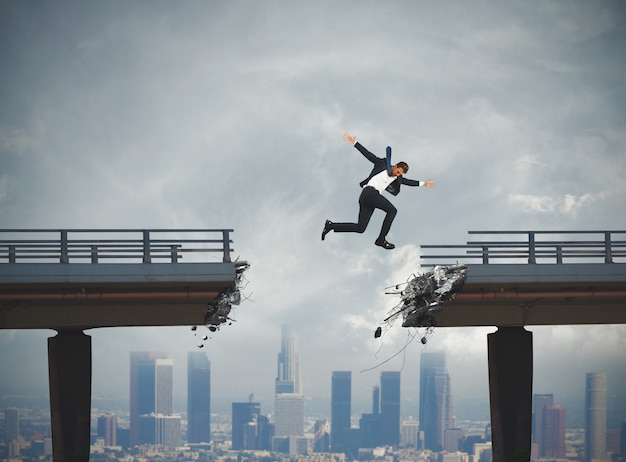 Empresário passa por uma ponte quebrada com um grande salto