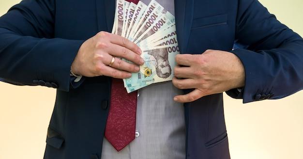 Empresário pega um maço de dinheiro ucraniano como suborno e se esconde no bolso dentro de uma jaqueta