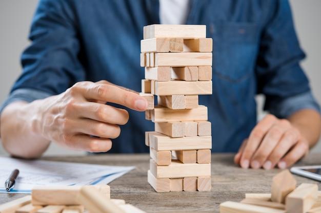 Empresário pegando um pedaço de construção de tijolos de madeira