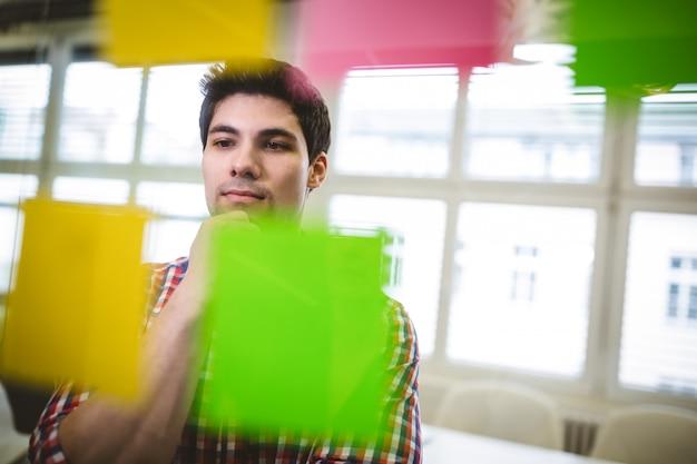 Empresário pensando enquanto olha para as notas autoadesivas