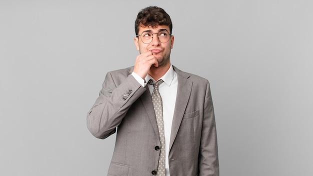 Empresário pensando, sentindo-se duvidoso e confuso, com opções diferentes, imaginando qual decisão tomar
