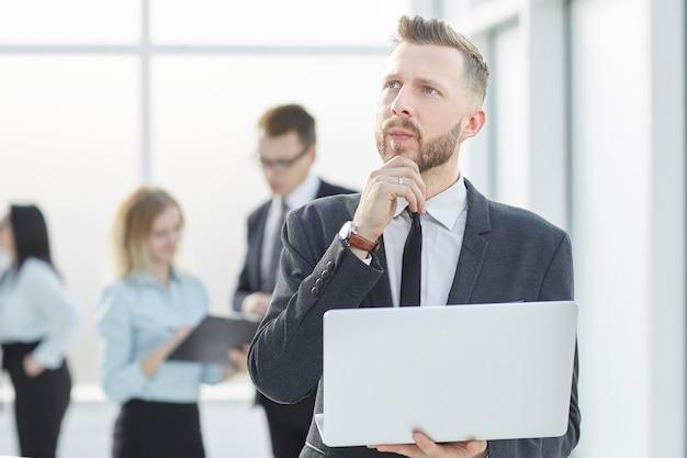 Empresário pensativo com laptop de pé no corredor do escritório.