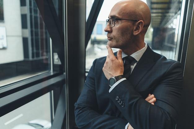 Empresário pensativo de terno com óculos, olhando para longe na janela ou no elevador de vidro