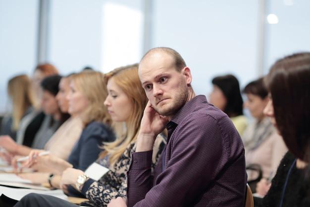 Empresário pensativo durante uma conferência de imprensa.