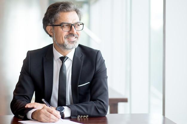 Empresário pensativo em terno fazendo anotações