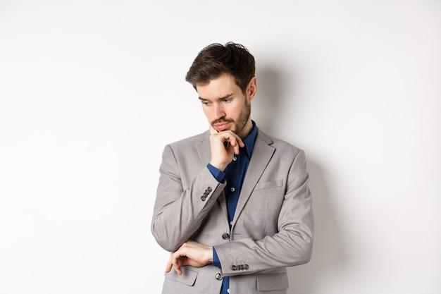 Empresário pensativo em terno olhando para baixo e pensando, tomando decisões, de pé sobre um fundo branco.