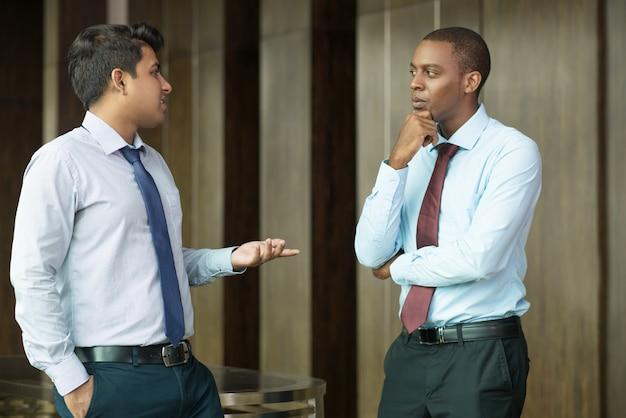 Empresário pensativo olhando seu parceiro de negócios falante