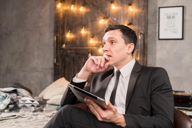 Empresário pensativo segurando o tablet