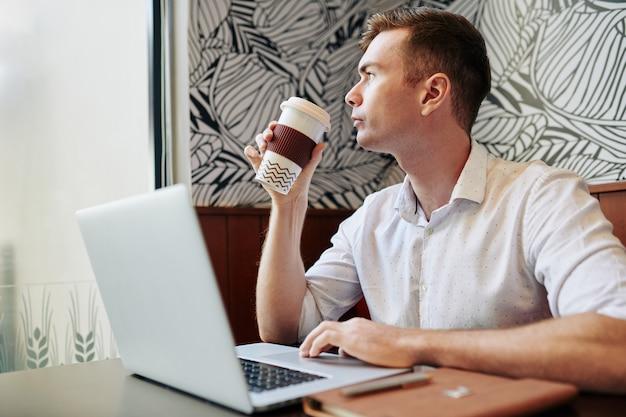 Empresário pensativo tomando café