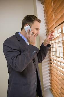 Empresário percorrendo persianas durante a chamada