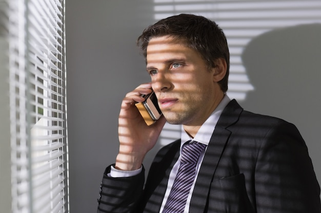 Empresário percorrendo persianas enquanto estava de plantão no escritório