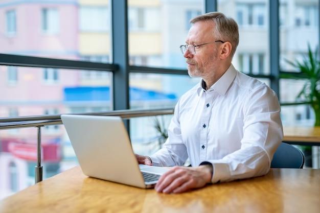 Empresário picando na mesa com o laptop. camisa branca. vista panorâmica da cidade.