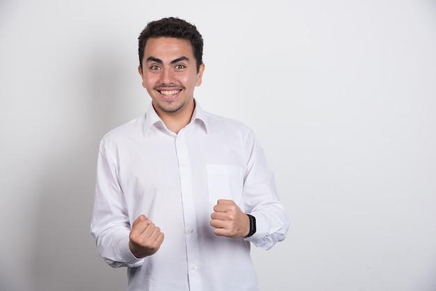 Empresário positivo em pé sobre fundo branco.