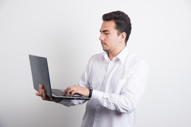 Empresário procurando laptop com expressão séria no fundo branco.