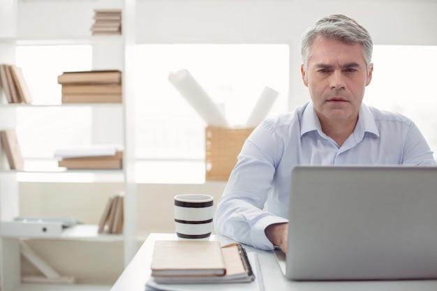 Empresário profissional. homem bonito e sério sentado à mesa do escritório e olhando para a tela do laptop enquanto faz seu trabalho