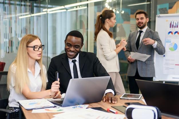 Empresário profissional preto e empresária caucasiana, sentados juntos à mesa da sala de reuniões e discutir os detalhes e a estratégia futura do seu projeto conjunto.