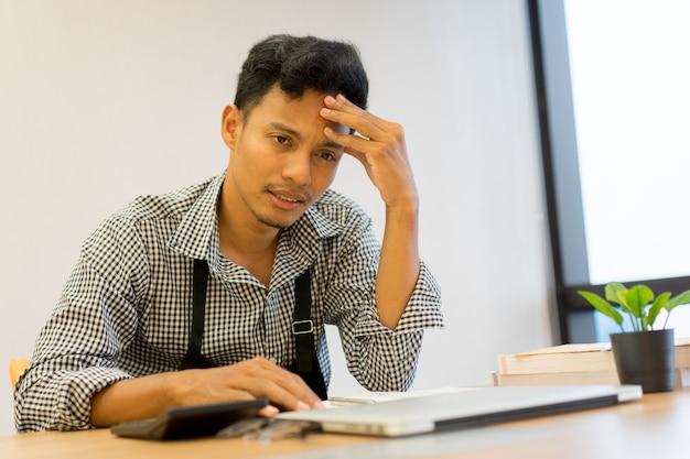 Empresário proprietário homem asiático estresse cefaléia com dívida