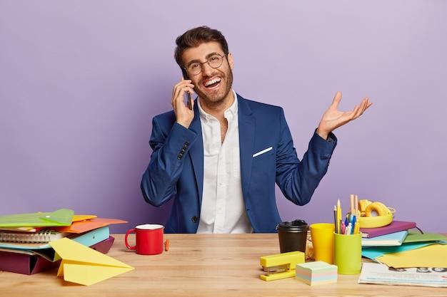 Empresário próspero sorridente fala no celular, sentado no local de trabalho