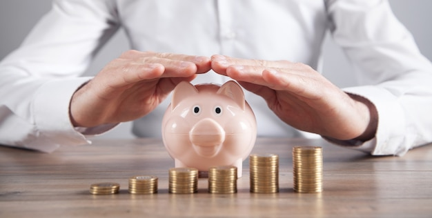 Empresário protege o cofrinho e as moedas. economizando dinheiro