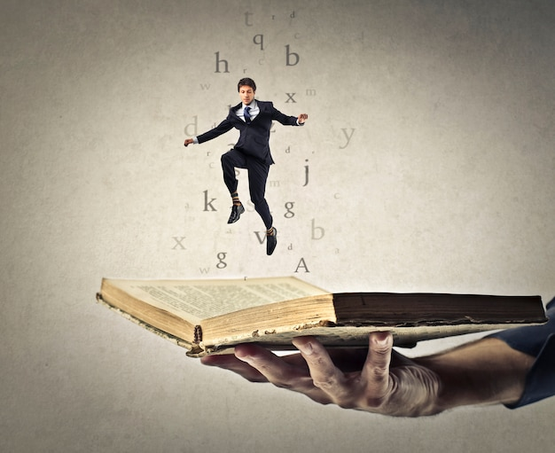 Empresário pulando de um livro