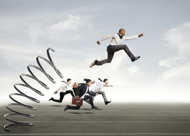 Empresário pulando em uma mola durante uma corrida com oponentes