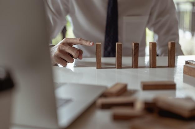 Empresário puxando ou colocando longos blocos de madeira em um escritório moderno indica o impacto