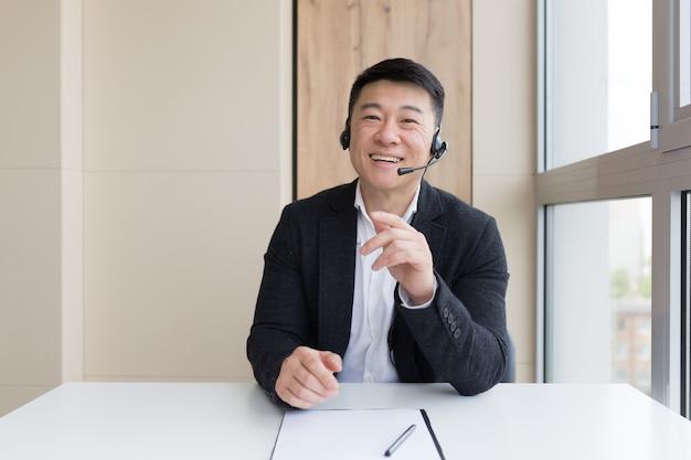 Empresário realiza consulta online explica com as mãos usando fone de ouvido