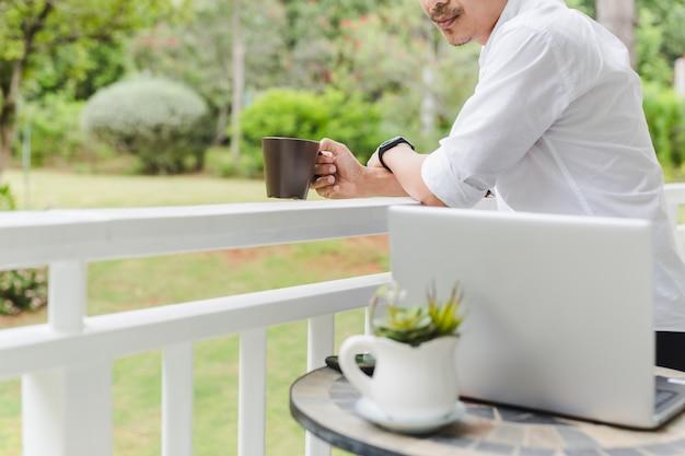 Empresário relaxa em pé na mão do terraço segurando café com o laptop na mesa.