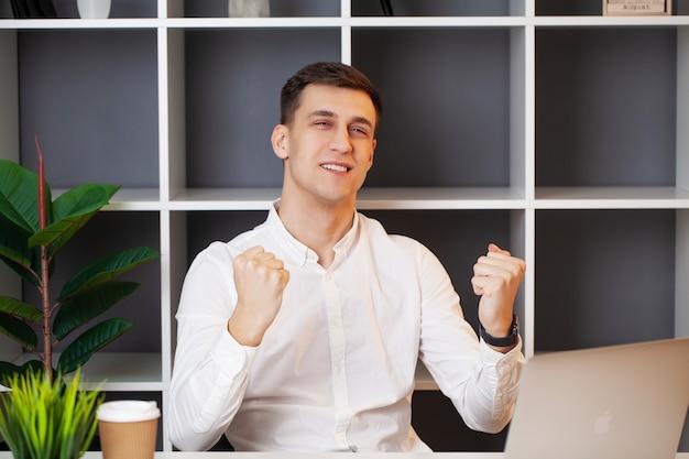 Empresário relaxado trabalhando com um laptop em seu escritório.