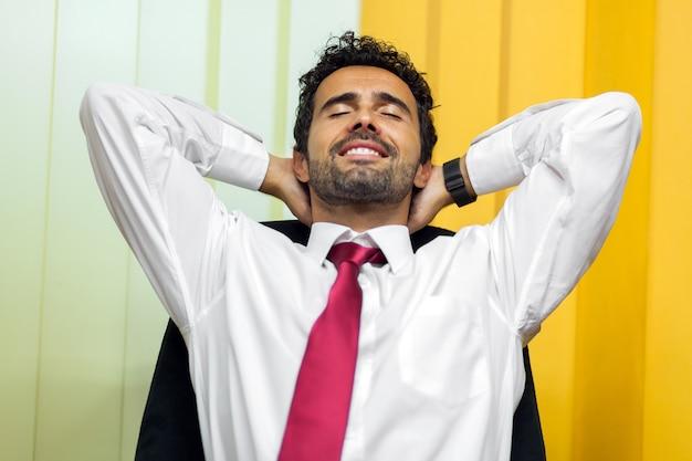 Empresário relaxante na sua cadeira depois de um árduo dia de trabalho