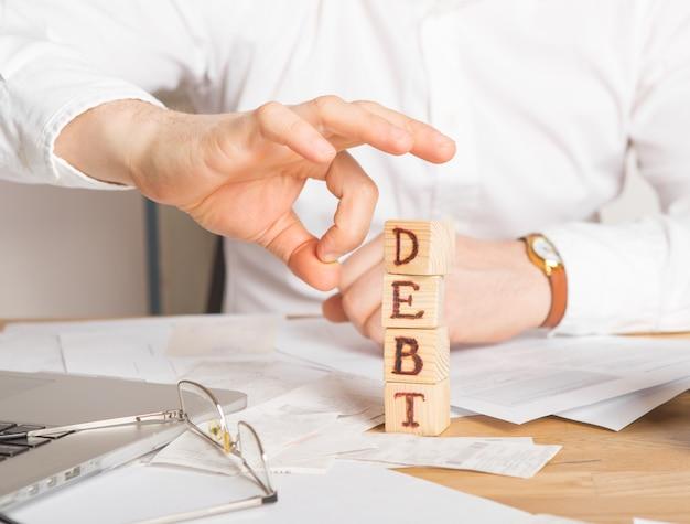 Empresário remove blocos de madeira com a palavra dívida. redução ou reestruturação de impostos. anúncio de falência. recusa em pagar empréstimos e invalidá-los.