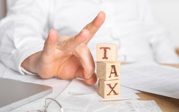 Empresário remove blocos de madeira com a palavra imposto. redução ou reestruturação da dívida. anúncio de falência. recusa em pagar empréstimos e invalidá-los.